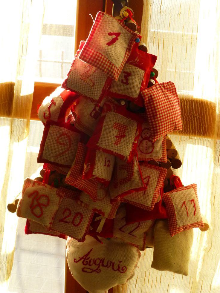 Mini albero di natale uso calendario dell'avvento decorato con 25 sacchetti che possono essere riempiti con delizie.