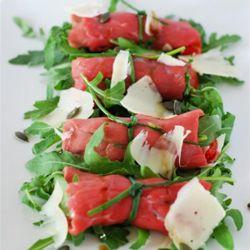 Involtini di carpaccio con rucola e pomodorini, vinaigrette all'olio di semi di zucca