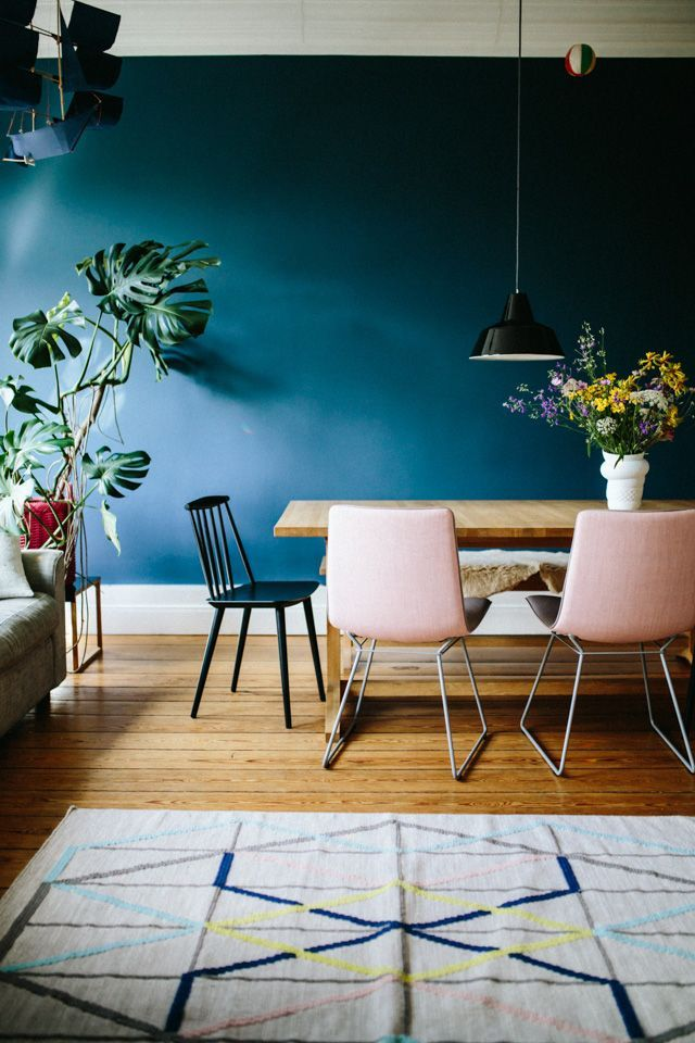 Dark blue walls and pale pink chairs in the dining room / Herz & Blut