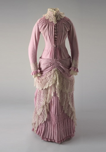1880s Two piece pink full length wool dress (bodice and skirt) with cream lace trimming. The pleated bodice has a high stand-up collar and is long-sleeved. Both cuffs and collar are trimmed with cream lace. Round copper buttons run down the centre-front and feature an anchor design. The skirt is pleated and layered with extra fabric and trimmed with cream lace.