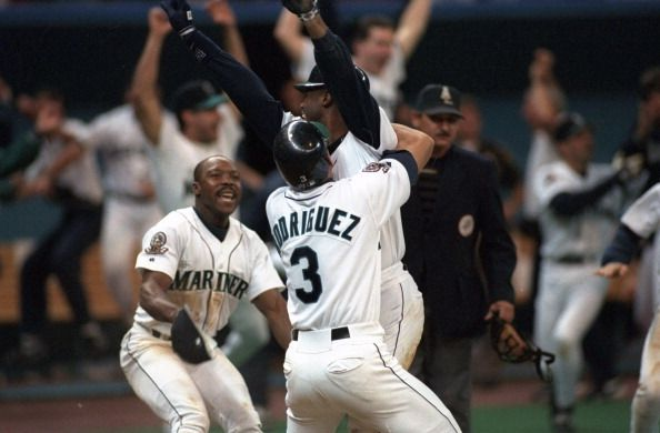 ALDS Playoffs Seattle Mariners Ken Griffey Jr victorious getting hugged by teammate Alex Rodriguez on field as Vince Coleman looks on after scoring...