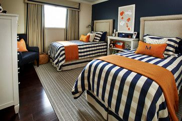 Navy and white stripe comforter with red blanket at foot of the bed with red pillow and navy monogram.