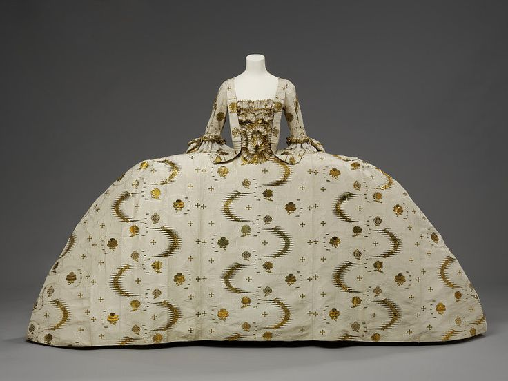 Mantua Court Gown, 1755, England. Although considered stylish daywear in the early 18th century, the mantua had become very old-fashioned by the 1750s and was worn only for court dress. Wide hoops were beginning to go out of style, but kept their extreme width at court. To make up for its conservative cut, court dress was always made from the most fashionable as well as expensive fabrics and trimmings.
