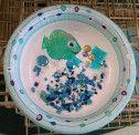 """A fish bowl craft for preschool or kindergarten. Paper bowl, aquarium gravel, foil, """"gems"""" and shiny paper fish."""