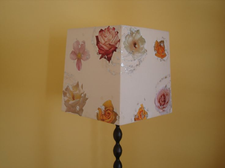 Decoupaged lampshade with fabric roses and small pieces of silver leaf.