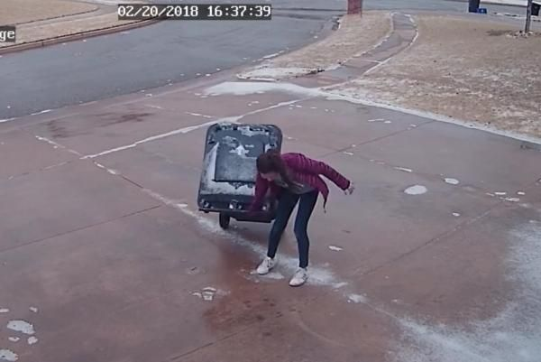 Oklahoma girl bringing in trash bin struggles on icy driveway