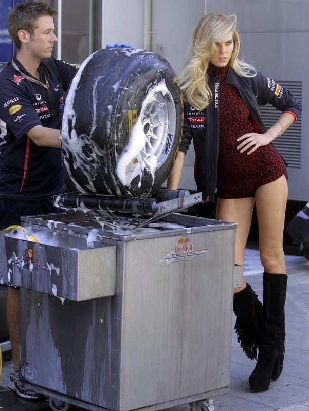 Ein Mechaniker von Red-Bull wird beim Reinigen der Reifen von einem Gridgirl abgelenkt. (Foto: Kai Försterling/dpa)
