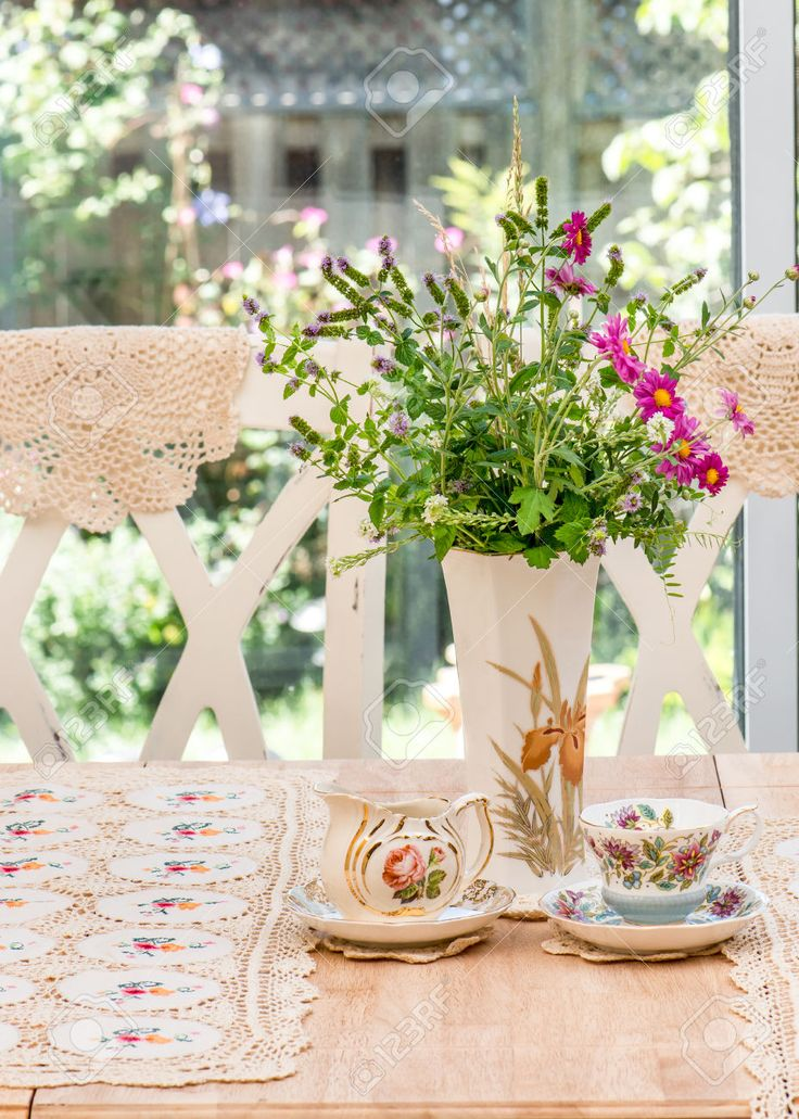 French country style afternoon tea table in the garden. Antique vintage  English fine bone china