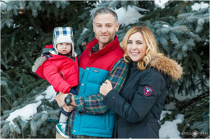 A cute family with a young son  get their family photos taken with a snow covered blue spruce tree near the Sebastian Hotel in Vail, CO. - April O'Hare Photography http://www.apriloharephotography.com