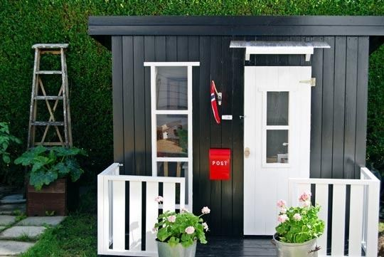 This eye-catching black and white playhouse in Norway complements the owners' full-size house which is painted white with a black door. It has charming details including a mailbox, flag and small flower garden. See more at Den Gode Feen.