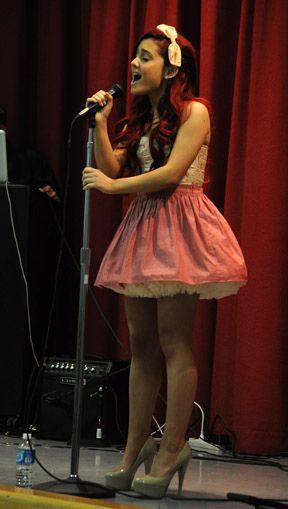 Ariana está llevando una cinta blanca y una falda rosa y los tacones altos gris. Los tacones altos cuestan cincuenta euros. La falda cuesta catorce dolares. La cinta cuesta cuatro euros.