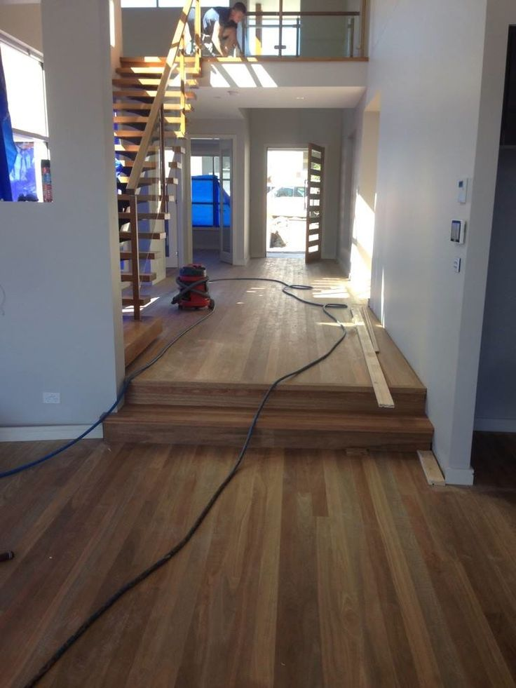 Spotted Gum timber flooring being installed into main foyer with step down to main living areas and staircase to upstairs bedrooms eetc