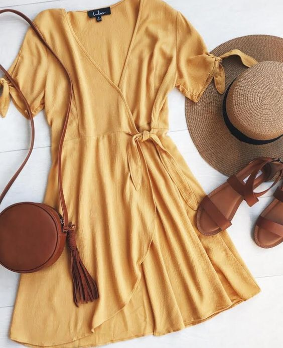 Golden yellow wrap dress with leather accessories and a wide-brimmed hat. Ultimate beach outfit!