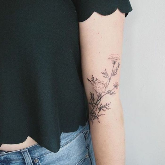 wildflower tattoo, woman with black cropped top, and blue jeans, with a tattoo of a wild flower, done with black ink, on her arm