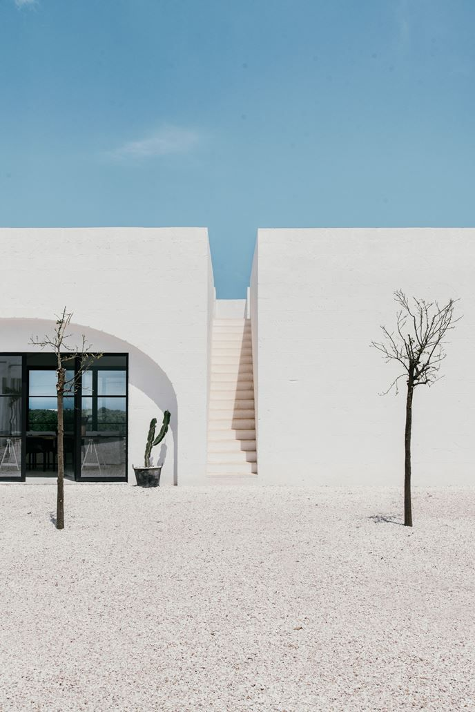 #Masseria Moroseta: a white stone farmhouse standing proudly on the ridge with views across the olive trees to the sea #white #Italy Project by Andrew Trotter Studio