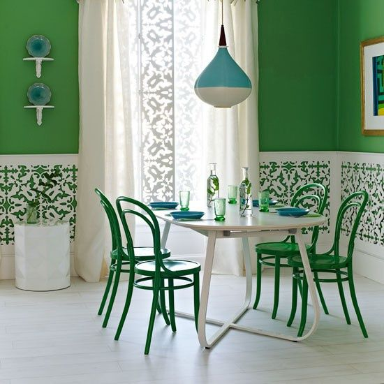 Mur vert, chaises vertes, table blanche, vase blanc, lustre bleu... Une salle-à-manger colorée !