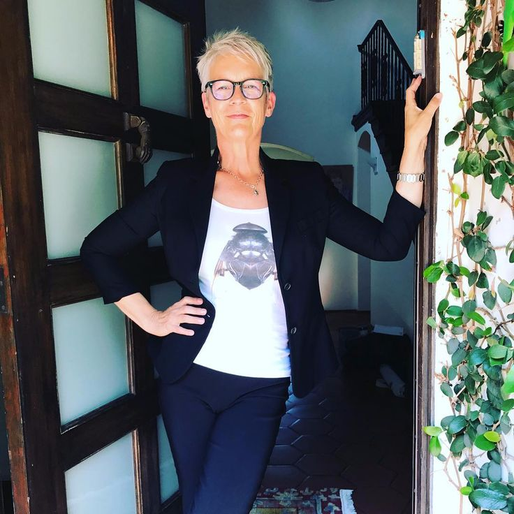 Jamie Lee Curtis standing at the door, with her hand on her waist