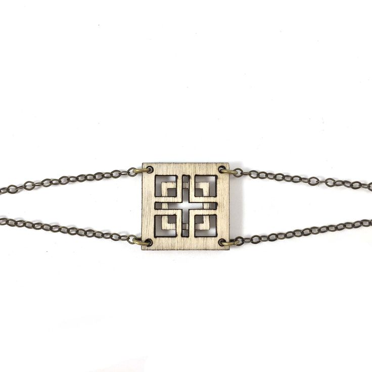 Total stunner that you'll love forever. This simple square bracelet is wood and features a simple cut out design and double chain closure. Perfect with everything from a rocker tee to a black jumpsuit.