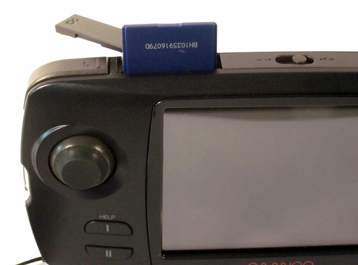 SD Card shown in the top-loading slot before being seated beneath the cover. The #Caanoo ships with a 2GB card, but can accept a 32GB SD Card. The volume control is to the right of the SD Card lot. To the left is the L-button used be the left index finger. At the base of the left side is a loop for attaching the wrist strap.  Read more: http://www.8-bitcentral.com/gphCaanoo/caanooImages.html#ixzz2nGRXYoZh