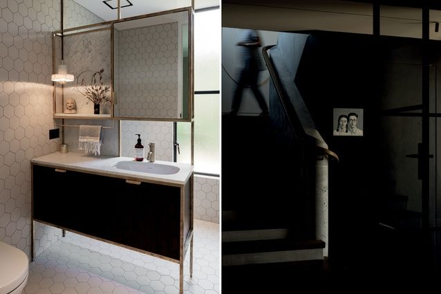 Bathroom featuring custom-made space dividers using brass joinery; looking through the internal glass doors towards the cast concrete stairs with bespoke oak handrail.