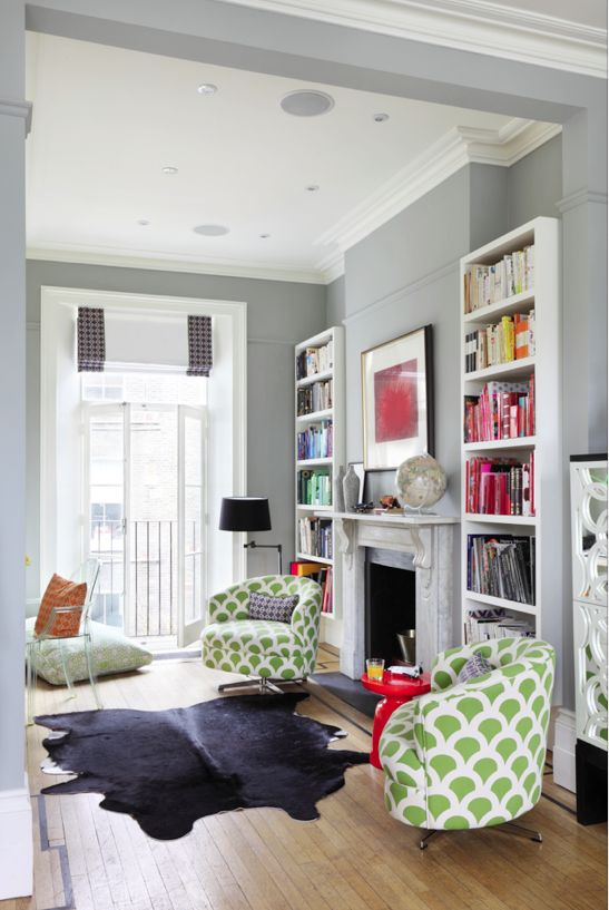 The subtle flecks of green on these cosy armchairs bring some playful pattern to this neutral room. While the colour co-ordinated books add the perfect splash to the white bookcases. Image: Livingetc