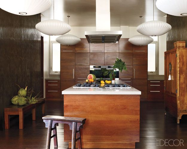 The cooktops and   hood are by Miele, the light fixtures are by George   Nelson, and the island of vesi wood is topped with   DuPont Corian.