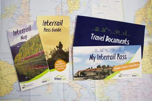 Image of the Interrail Travel Pack including an Interrail Pass Guide, Pass Cover, Map and Travel Wallet laid on a map of Europe.