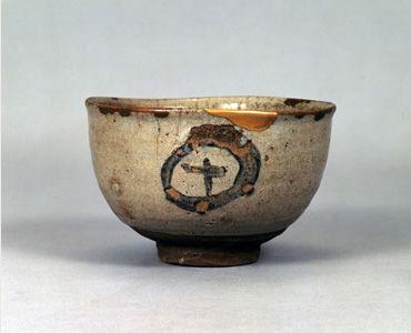 絵唐津丸十文茶碗 - 出光コレクション - 出光美術館 桃山時代 ゆったりとして、大らかな茶碗である。腰に丸みをもちながら立ち上がり、口縁はやや外反している。灰青色を帯びた釉が腰まで包み、腰から高台にかけては、赤褐色に焼けた素地をみせる。胴には、太く粗い筆致で、円の中に十を描く。文様の部分は釉が剥がれ落ち、虫喰いとなっている。出光佐三は本作を、その文様から「丸十の茶碗」と呼んで鍾愛した。出光美術館の古唐津コレクションは、この一碗と佐三との出逢いから始まる。