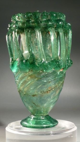 Roman green glass jar with handles. 5th-6th century AD. Height 15.5 cm. (6 18 in.). diagonal spiral ribbing, tapering cylindrical neck, vertical short rim and folded tubular flange.