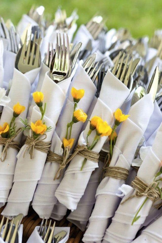 Cubiertos envueltos en servilletas de tela blanca y amarrados con cordel. Como detalle un par de flores silvestres puestas cerca del nudo.