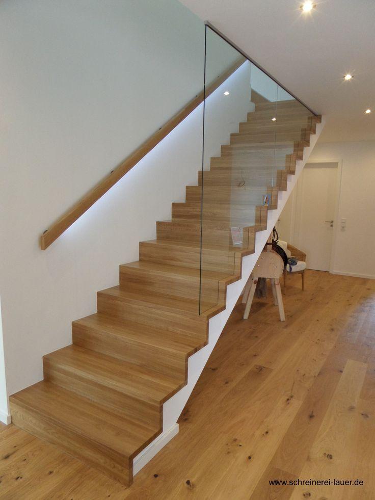 Treppenbelag aus Eiche Massivholz und Handlauf mit integriertem LED. Die Glasscheibe wurde für ein harmonisches Gesamtbild abgestuft und in den Stuf
