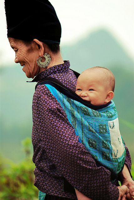 Grandmother carrying Laughing Baby on her back.