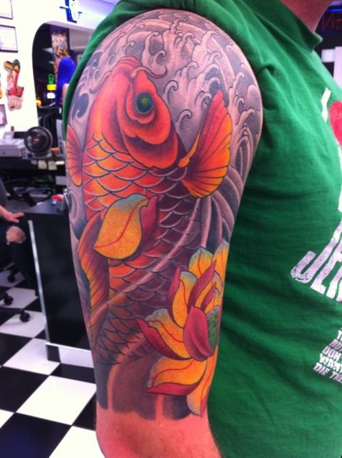 Orange koi with lotus tat This colorful koi tattoo features the bright orange fish swimming upstream in gray waters in this man's half arm sleeve. Half sleeve koi tattoo with fish for men