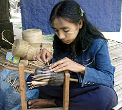 Some of the finest lacquerware containers are made by weaving horsehair between fine splints of bamboo before the lacquer sap is applied, as this woman is doing. The resulting containers are remarkably flexible