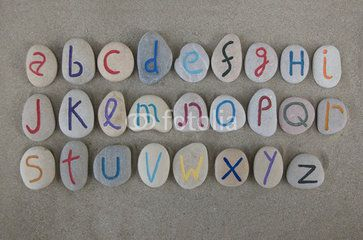 Alphabet set on carved stones over the sand
