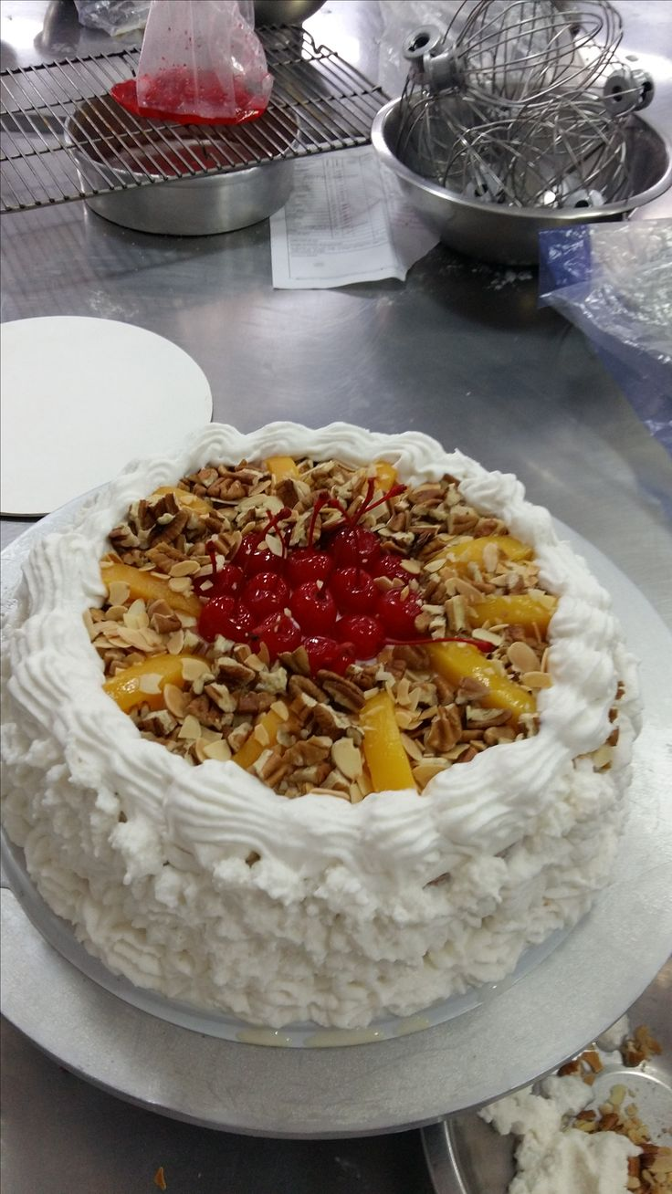 Pastel de 3 leches decorado con chantilly, cerezas rojas, nueces, almendras y duraznos,
