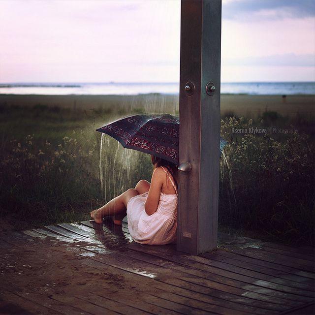 Sitting under a beach shower.