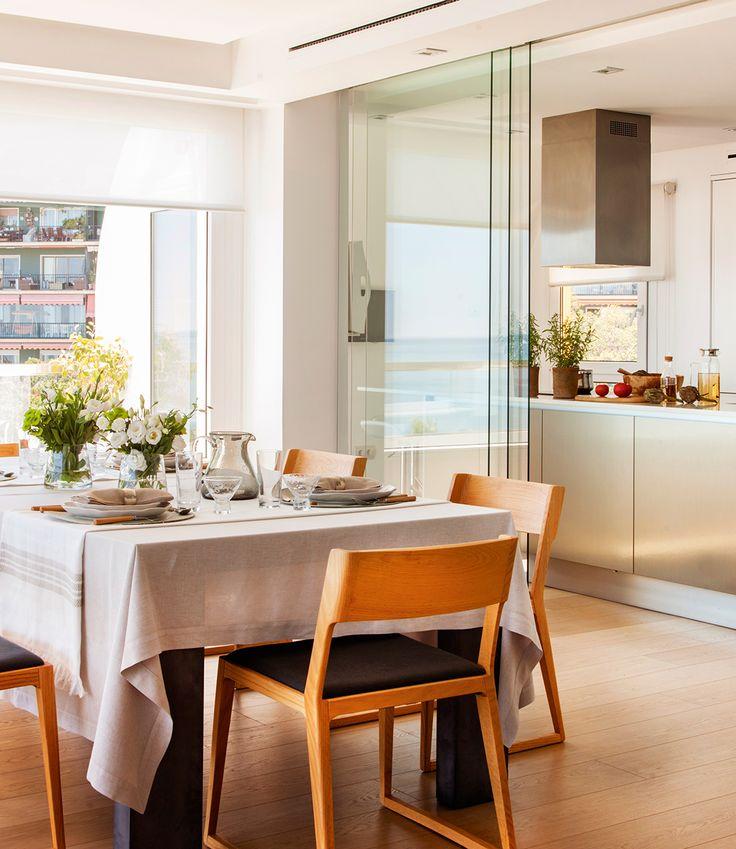 Comedor comunicado con la cocina con unas puertas correderas de cristal