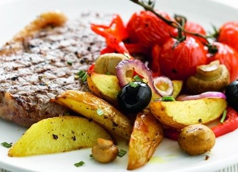 Ovengebakken aardappelen met kerstomaten, rode ui en gegrilde biefstuk
