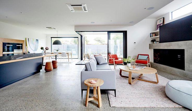 Sala de estar com piso de granilite, sofá cinza lareira contemporânea, poltrona laranjada, parede azul escuro. Mesa de centro de madeira e banquinho de madeira. Casa Art Decoração de interiores por Archer Interiors
