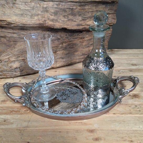 Σετ γάμου αποτελούμενο από vintage οβάλ δίσκο με καθρέφτη σε γκρι-γαλάζιο χρώμα, κρυστάλλινο ποτήρι κρασιού με ιδιαίτερο σχέδιο, γυάλινη καράφα με ασημί λεπτομέρεια και vintage χειροποίητα στέφανα γάμου από πέτρες σε ιβουάρ και μόκα χρώμα. Η πρόταση αυτή είναι ενδεικτική του NEDAshop.gr και μπορεί τα τροποποιηθεί όπως εσείς θέλετε ή μπορείτε να δημιουργήσετε το δικό σας εξαρχής στις υποκατηγορίες του γάμου…