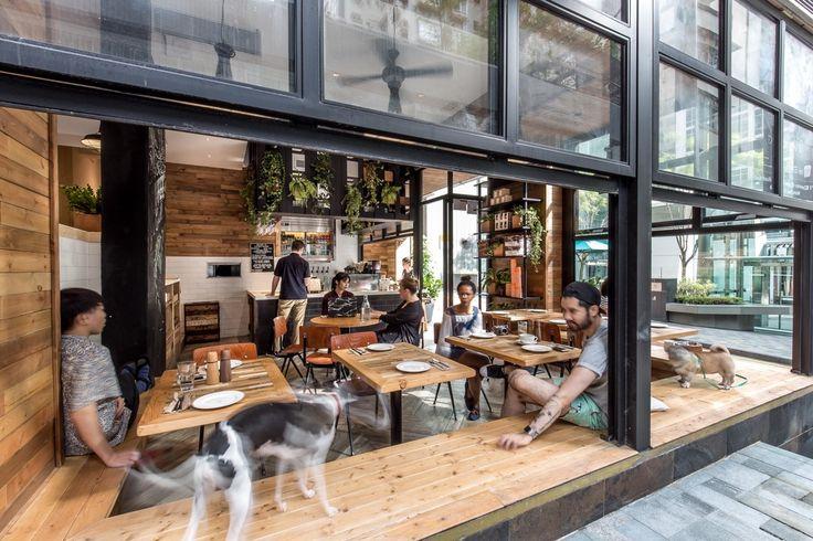 壁際に縁側的なベンチシートのある開放的なカフェのダイニング サイドから