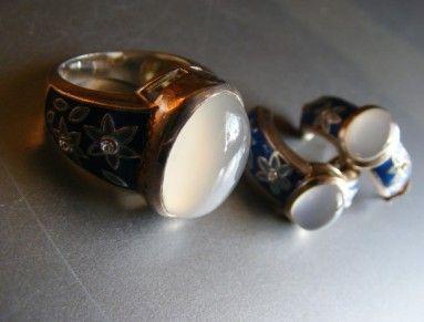 Prsten ze stříbra a přihrádkového smaltu - email. Osázený měsíčním kamenem a zirkony. Masivní šperk. Prsten doporučuji nosit samostatně.   Kabošon je o velikosti cca 1,8 x 1,3 cm. Šíře celkem cca 1,9 cm, šíře v nejširším místě obroučky se smaltem - pod kabošonem - cca 1 cm.   Obroučka je silná, prsten poměrně široký. Vnitřní průměr v cm cca 1,8 -1,9 cm, na trnu 57. Nedoporučuji zmenšovat, či zvětšovat. Emaily by mohly popraskat ! Skvělý stav a posilující šperk.   Ag 925/1000 v 11,81g…