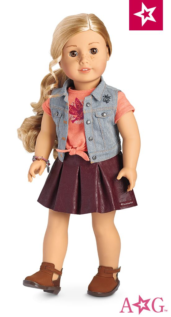"""Tenney™ Doll & Book. The 18"""" Tenney doll has light brown eyes that open and close, freckles on her nose, and long, curly blond hair. Tenney's unique hand positioning helps her hold her guitar, banjo, and pick! She arrives in a graphic tee, denim vest, faux-leather skirt, and ankle boots. Also included are a woven bracelet and the Tenney paperback book.  $115"""