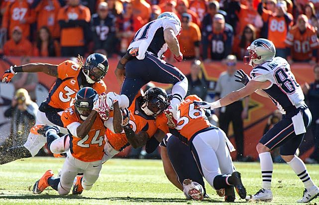 Julian Edelman #11 (WR) tries to go over the Denver defense for extra yards. He led the Patriots with team highs in receptions (10) and yards (89) and scored their only touchdown.