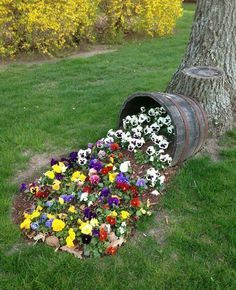 Flowers spilling out of barrel. This but the bucket at an upward angle more and simpler with the flowers
