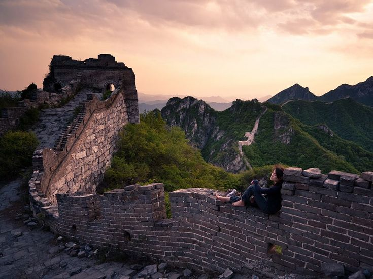 A woman rests on Jiankou Great Wall, a section of the Great Wall of China near Xizhazi Village.