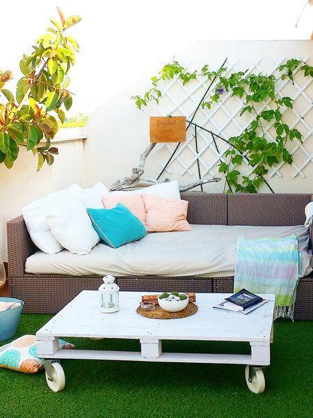 Terraza con sofá, mesa y césped artificial
