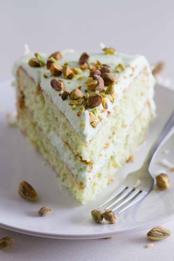 Reminiscent of the popular Watergate Cake, this Coconut and Pistachio Pudding Cake is not only pretty, but tasty as well! Moist and flavorful, this coconut and pistachio cake is topped with a creamy pistachio cream cheese frosting which takes it a step up from the traditional cake.