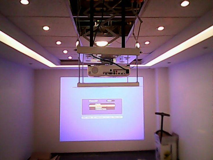 Proyector instalado en techo con soporte eléctrico